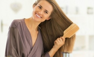 Happy young woman combing hair in bathroom